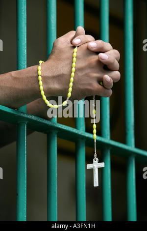 The Philippines, Prisoner behind bars praying the rosary - Stock Photo