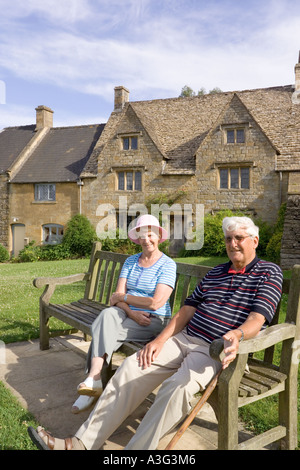 Visitors enjoying the early evening sunshine in the Cotswold village of Guiting Power, Gloucestershire - Stock Photo
