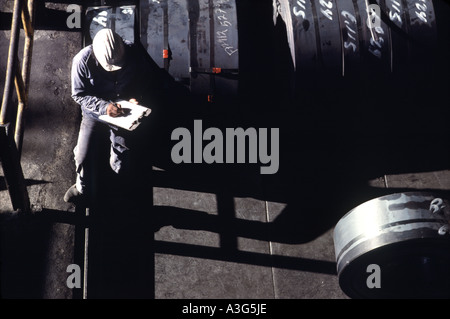 Overhead view of engineer in a white hard hat sitting down to take notes on an offshore oil drilling platform.
