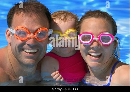 Portrait of happy family in swimming pool - Stock Photo