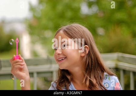 A little girl blowing bubbles - Stock Photo