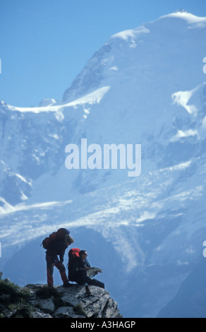 couple walking in the French mountains near Chamonix with Mont Blanc summit in the background - Stock Photo
