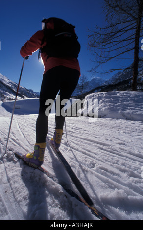 woman cross country skier using a skating step to cover the tracks - Stock Photo