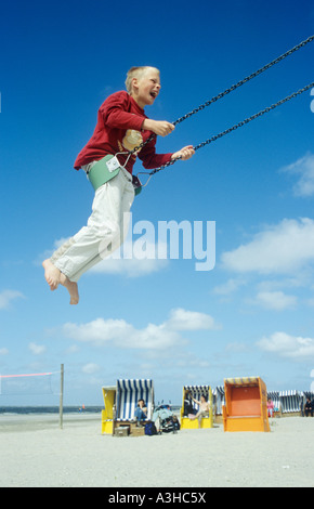 a young boy on a swing at the beach of Norderney Island in Northern Germany - Stock Photo