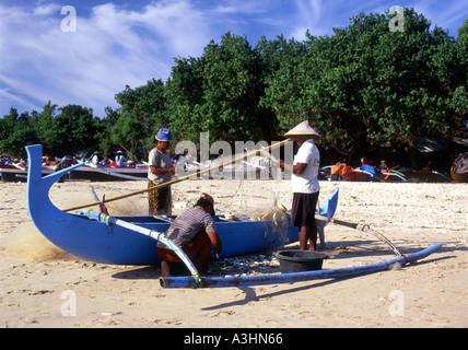 local men at work on their fishing boat on kuta beach bali indonesia - Stock Photo