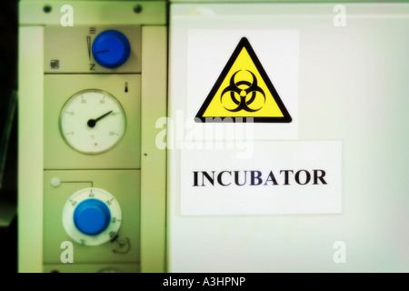 Biohazard warning sign on door of incubator in bio science research lab - Stock Photo