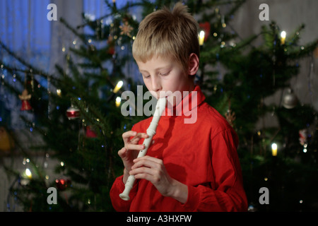 young boy playing the recorder in front of a Christmas Tree - Stock Photo