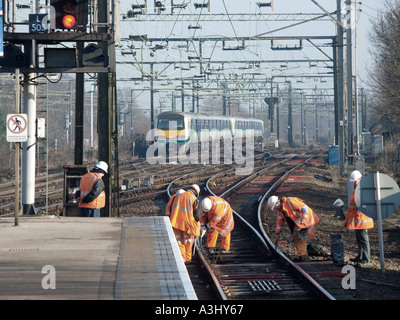 Main line railway with maintenance workers in high visibility safety clothing working on track - Stock Photo