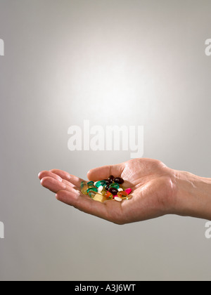 Person holding pills and capsules - Stock Photo