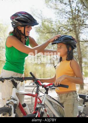 Mother putting bicycle helmet on girl - Stock Photo