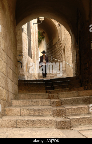 Religious Jew walking through narrow cobbled alley at the Jewish quarter, old city East Jerusalem, Israel - Stock Photo