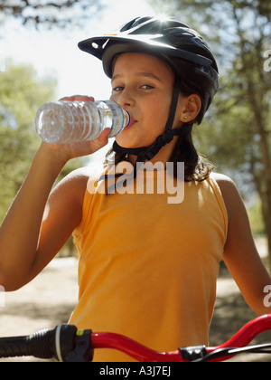Girl on a bike drinking water - Stock Photo