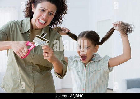 Mother cutting up a credit card - Stock Photo