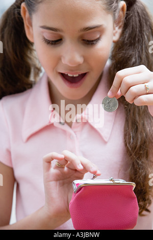 Girl holding a coin and purse - Stock Photo