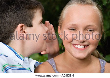 Boy whispering to girl - Stock Photo