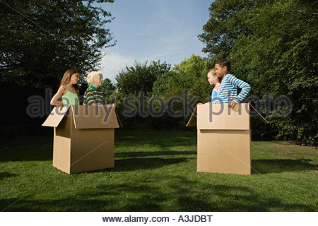 Kids in cardboard boxes in garden - Stock Photo
