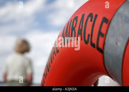 Life saver in foreground on board a cruiseship with in the background a woman watching the ocean - Stock Photo