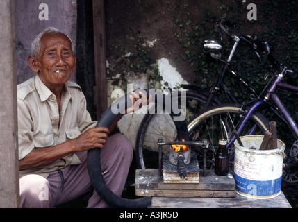 elderly local man at his roadside bicycle repair shop madiun east java indonesia - Stock Photo