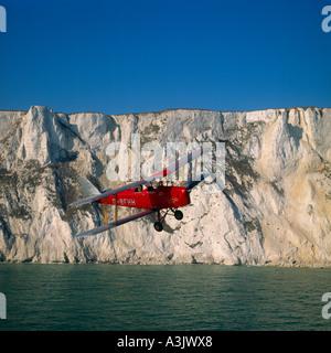 de Havilland DH82 Tiger Moth against White Cliffs Dover England - Stock Photo
