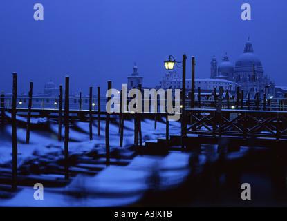 Venice in snow View over gondolas on Molo to Santa Maria della Salute at night dawn Venice Veneto Italy - Stock Photo