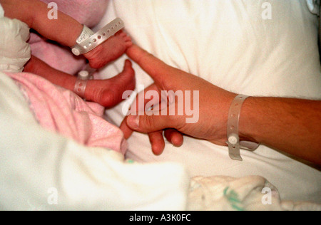 Father touching newborn baby's feet after delivery. Edina Minnesota USA - Stock Photo