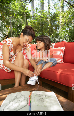 Mother Helping Daughter Tie Shoes - Stock Photo