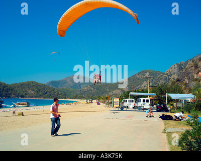 Paragliders landing on the beach at Oludeniz - Stock Photo
