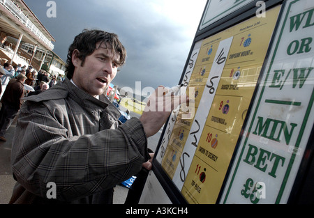 Bookie writing up the odds at his stand at Lingfield. - Stock Photo