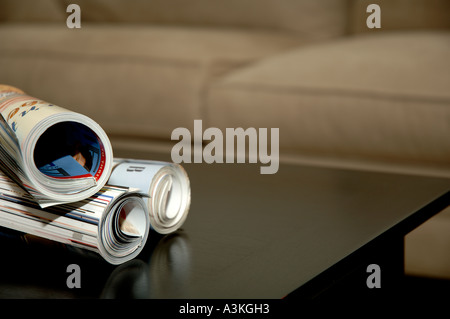 Rolled up magazines over coffee table - Stock Photo