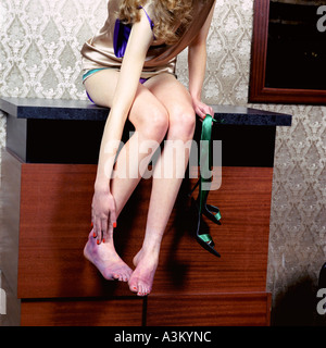 young woman sitting on chest of drawers rubbing her aching feet - Stock Photo