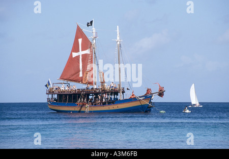 Off Sandy Lane Bay west coast beach Jolly Roger tourist day trip fun sail boat moored - Stock Photo