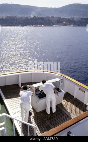 Officers checking instruments on wing bridge of cruise ship approaching Sorrento Mediterranean - Stock Photo