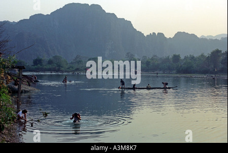 Men in canoes cast nets to catch fish in late afternoon, on the Nam Xong River, Vang Vieng, Laos. DN23 - Stock Photo