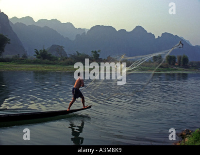 Men in canoes cast nets to catch fish in late afternoon, on the Nam Xong River, Vang Vieng, Laos. DN24 - Stock Photo