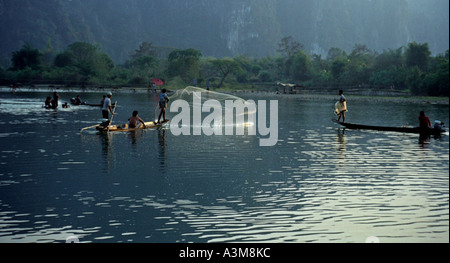 Men in canoes cast nets to catch fish in late afternoon, on the Nam Xong River, Vang Vieng, Laos. DN28 - Stock Photo