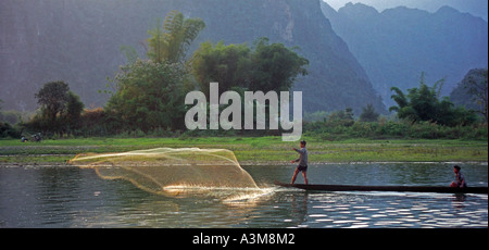 Men in canoes cast nets to catch fish in late afternoon, on the Nam Xong River, Vang Vieng, Laos. DN32 - Stock Photo