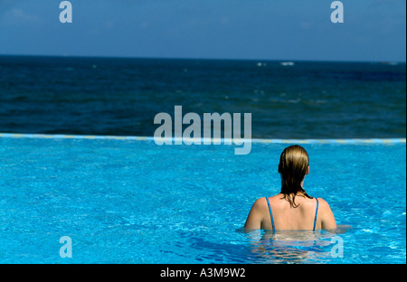 Woman in the infinity pool at Saman Villas hotel near Bentota in Sri Lanka. - Stock Photo