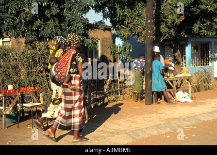 A neighborhood in Maputo Mozambique with women walking and carrying babies over their backs wrapped in shawls - Stock Photo