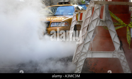 smoke, steam steam pipe leaking in street - Stock Photo