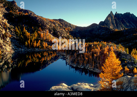 Inspiration Lake surrounded by fall larches with Prusik Peak in the background Enchantment Lakes Alpine Lakes Wilderness - Stock Photo
