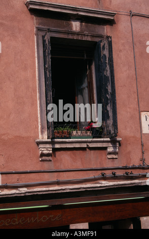 Worn and peeling paintwork on window shutters in Venice Italy - Stock Photo