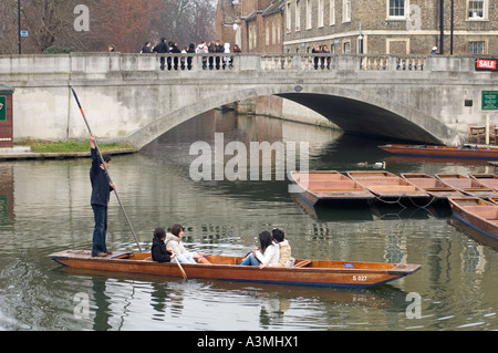 Japanese tourists leaving setting off in a punt in Cambridge - Stock Photo