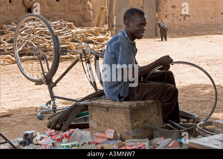 Local village man and his bicycle repair business in Northern Ghana - Stock Photo