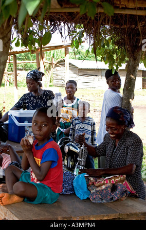 Ghanaian woman seamstress and family using hand operated sewing machine West Africa - Stock Photo
