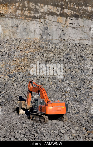 An orange excavator at the bottom of a rock quarry collecting the rock blocks blasted out of the bedrock - Stock Photo