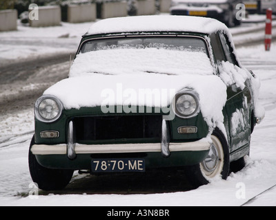 Classic car British racing green Triumph Herald covered in snow Dutch license plate Breda the Netherlands - Stock Photo