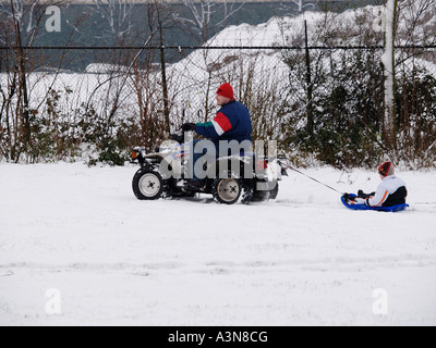 Father riding quad bike pulling towing his son through the snow on a sled sleigh winter fun Breda the Netherlands - Stock Photo
