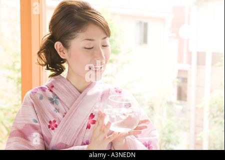 A young woman wearing yukata holding glass bowl
