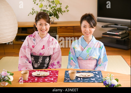 Two young women wearing yukata sitting - Stock Photo