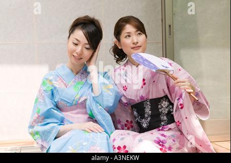 Two young women wearing yukata sitting on porch - Stock Photo